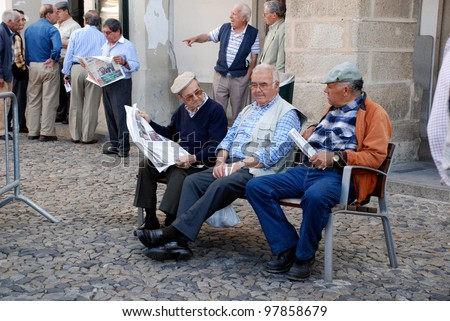 EVORA,PORTUGAL-MAY 03:Old men on bench reading newspapers and discussing news on May 03,2009 in Evora,Portugal. Evora is ranked number two in Portugal most livable cities survey of living conditions.