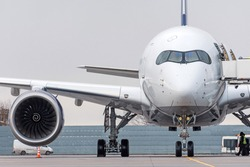 Exactly front view of the cockpit and nose, wing and engine of the aircraft at the airport
