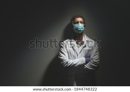 Exahusted COVID Doctor Leaning Against Wall in Secluded Hallway Stock photo ©