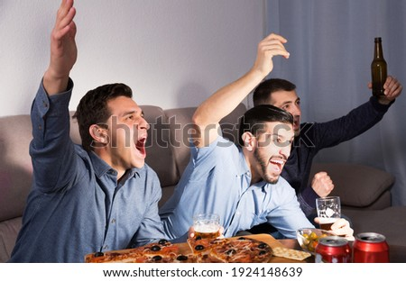 Exalted active male friends watching tv together at home, enjoying beer and pizza at home Foto stock ©