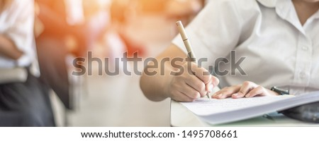 Exam at school with student's taking educational admission test in class, thinking hard, writing answer in university classroom, education and world literacy day concept