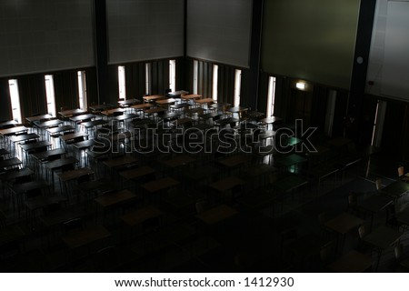 Examination hall at a university, with the lights out waiting for the exams to start.  Desks and chairs silhouetted against the windows.