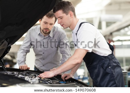 Examining a car Confident auto mechanic examining car engine while customer looking at it