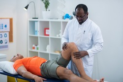 Examining knee. Physical therapist examining knee of sportsman lying near him after getting injury