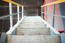 Example of chemical plant steampunk retro style interior part, with copyspace. Abstract image of industrial textured rusted stairs going down.