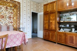 Example of Old Soviet Russian poor interior in Khruschev House. Aged  sideboard, table, chairs, sofa. Shabby floor. Tattered wallpaper on the wall. Apartment of pensioners. Selective focus.
