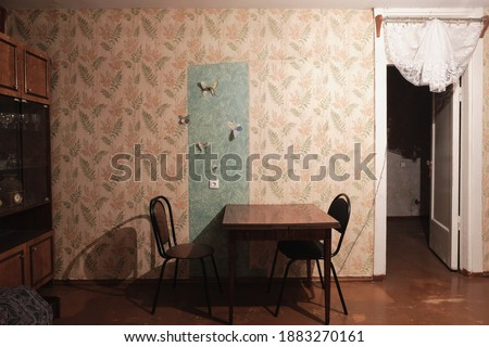 Example of Old Soviet Russian poor interior in Khruschev House. Aged  sideboard, table, chairs, sofa. Shabby floor. Tattered wallpaper on the wall. Paper butterflies as decor. Apartment of pensioners.
