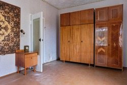 Example of Old Soviet Russian poor interior in Khruschev House. Aged table, chairs, sofa. Shabby floor. Tattered wallpaper and carpet as decor on the wall. Apartment of pensioners.