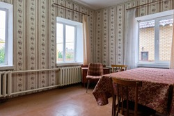 Example of Old Soviet Russian poor interior in Khruschev House. Aged table. Shabby floor. Tattered wallpaper on the wall. Apartment of pensioners.