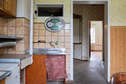 Example of Old Soviet Russian poor kitchen interior in Khruschev House. Aged  sideboard, table, chairs. Shabby floor. Tattered tiles on the wall. Apartment of pensioners.