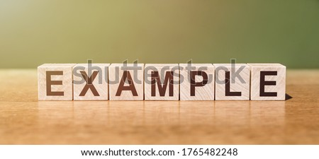 EXAMPLE word written on wooden blocks on wooden table. Concept for your design ストックフォト ©
