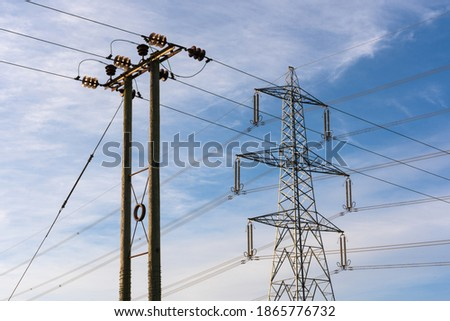 Examples of two overhead electricity pylons. Lattice steel pylon and a wooden pole pylon. Hertfordshire. UK Photo stock ©