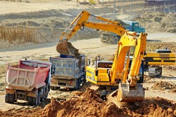 Excavation and loading onto dump trucks with excavators. The work of construction equipment in the production of earthworks