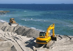 Excavator and bulldozer being used to construct sea defenses on the beach