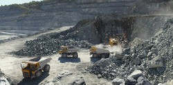 Excavator and heavy mining dump trucks in a limestone quarry, loading of stone ore, industrial panorama.
