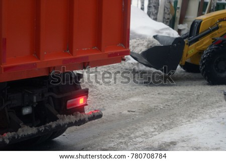 Excavator and lorry clean roads, streets from snow and ice. Winter industrial background #780708784