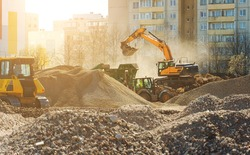 Excavator and screener machine working on construction site.