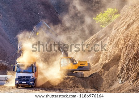 Excavator and truck for construction site. Excavation is the process of moving earth, rock or other materials with tools, equipment or explosives. It includes earthwork, trenching, wall and tunneling.