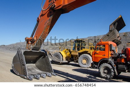 Excavator and trucks in his career. mining equipment. Mining