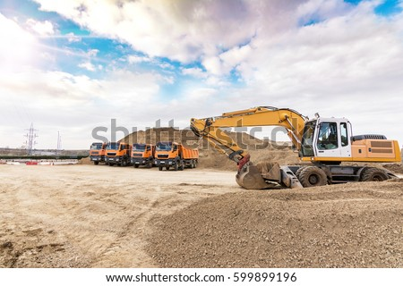 Excavator and trucks working on the excavation works of a road, moving rock and earth