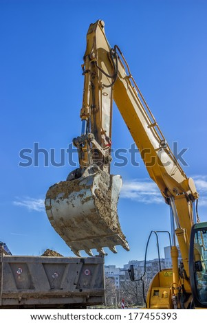 excavator arm and dumper truck digging trench for sewer line