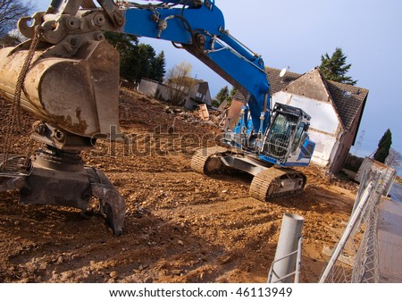 Excavator at demolition site in abandoned town in Germany. In this place will be a coal open-pit mine soon.