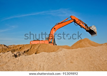 Excavator at sandpit with raised bucket over sky