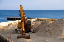 Excavator at sea straightens the sand for the beach.