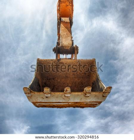 Excavator bucket on blue sky, Industrial excavator machine, focus on excavator bucket
