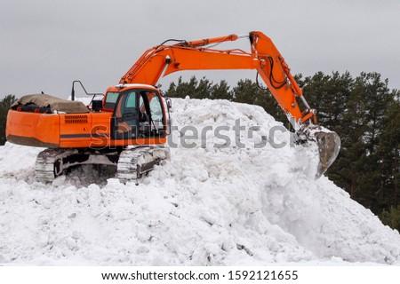 Excavator bucket takes snow, heavy equipment work