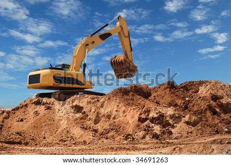 Excavator bulldozer in sandpit with raised bucket over blue cloudscape sky