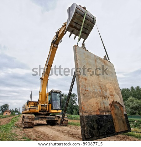 Excavator carries a large metal table