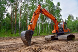 Excavator clearing forest for new development. Orange Backhoe modified for forestry work. Tracked heavy power machinery for forest and peat industry. Logging, road construction in forests