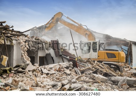 Excavator demolishing barracks for new construction project. Made with shallow depth of field.