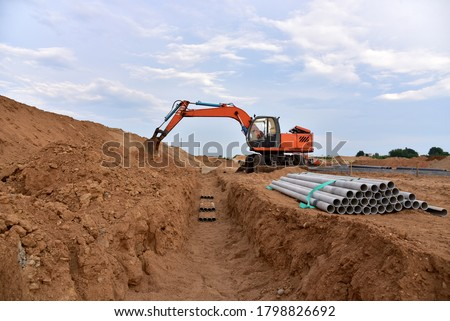 Photo of  Excavator dig the trenches at a construction site. Trench for laying external sewer pipes. Sewage drainage system for a multi-story building. Civil infrastructure pipe, water lines and sanitary storm