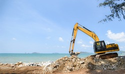 excavator digger stone working on construction site / backhoe loader on the beach sea ocean and blue sky background