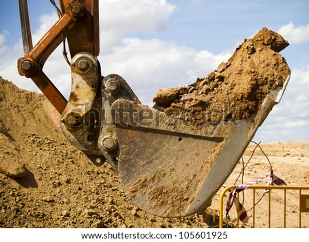 Excavator digging a deep trench, working, sand