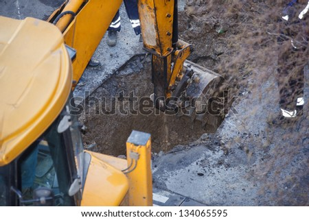 excavator digging a hole, breaking street asphalt, repairing damaged water supply pipe