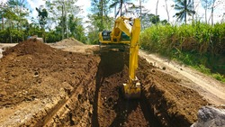 Excavator digging a trench, Work on the construction site.