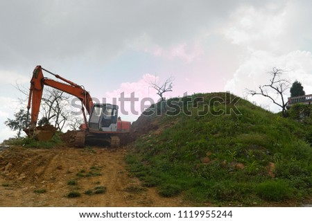Excavator digging land. Construction site with heavy machinery equipment on the hill. Sa Pa, Vietnam