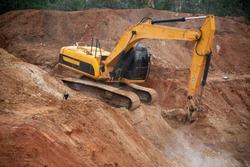 Excavator drilling on top of rocks at foundation infrastructure construction site