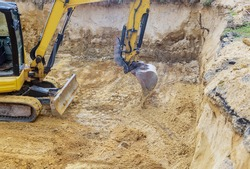 Excavator during earthworks backhoe on work digs ground during earthworks for the foundation