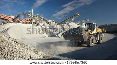 Excavator front end loader works against the background of equipment at a mining plant, panorama. Mining industry.