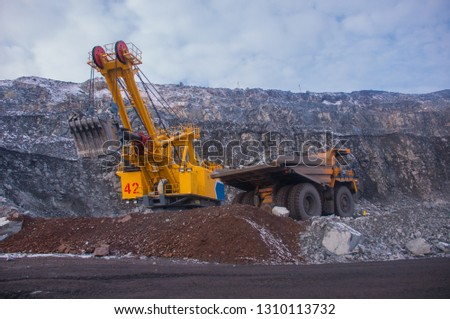 Excavator in the quarry loads the dumper with iron ore. Loading in winter #1310113732