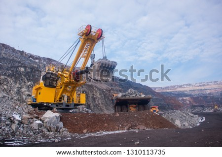 Excavator in the quarry loads the dumper with iron ore. Loading in winter #1310113735