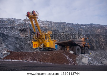 Excavator in the quarry loads the dumper with iron ore. Loading in winter #1310113744