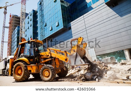 excavator is digging rubble in front of a modern building in construction
