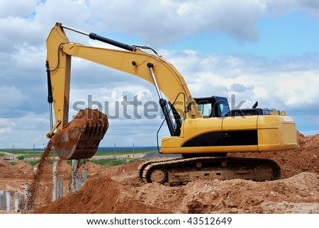 Excavator loader at construction site with sand in bucket over cloudscape sky
