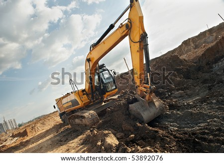 Excavator loader excavating soil from sandpit in summer