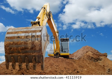 Excavator Loader standing in sandpit with pulled down bucket over cloudscape sky